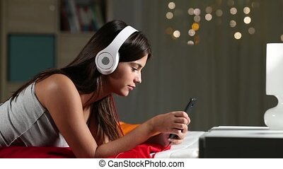 Teen listening to music relaxing on a bed