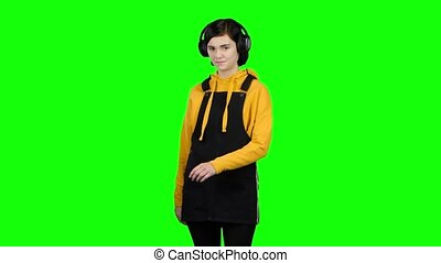 Teen listens to music on headphones. Green screen - Teen...