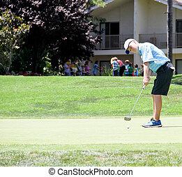 Teen male golfer putting 1 - Male teen golfer putting in...