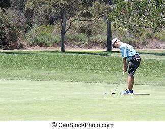 Teen male golfer putting 2 - Male teen golfer putting on...