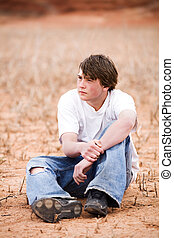 teenager sitting amongst the weeds in a dry lakebed. Natural-looking teen, simple clothing, ripped jeans, shot in Wyoming with copyspace.