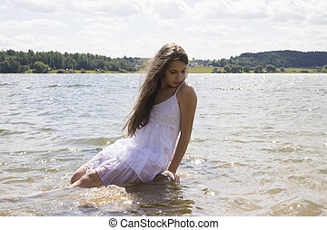 Teen mermaid girl in the lake