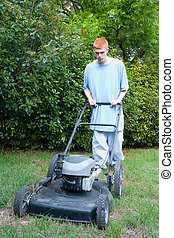 Teen Mowing Lawn 2 - Red-haired teenaged young man mowing...