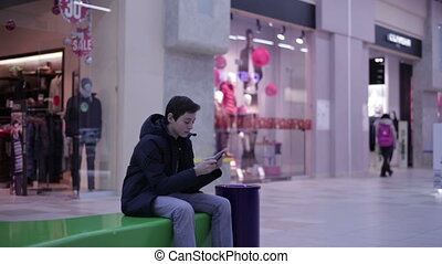Teen on a bench and playing phone