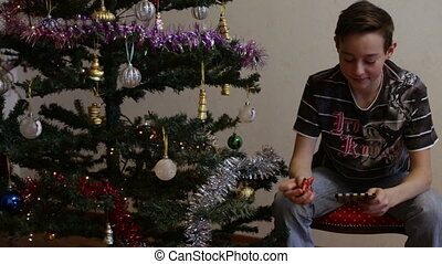 Teen opening Christmas gift near Christmas tree