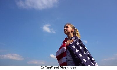 Teen patriotic woman with USA flag in nature - Side view of...