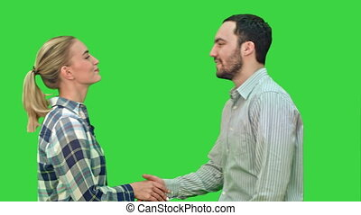 Teen people shaking hands and looking at camera on a Green Screen, Chroma Key.
