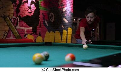 Teen playing pool billiard takes aim and hits ball