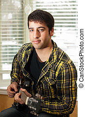 An attractive teenage boy looks at the camera while playing an electric guitar