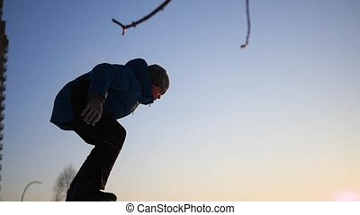 teen plays on the Playground in winter. flips in the snow at sunset