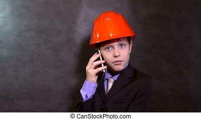 teen portrait boy builder in helmet smiling talking on phone smartphone