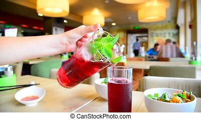 Teen pours fruit mint lemonade into glass in cafe