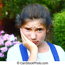 teen pretty girl with toothache outdoor portrait