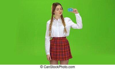 Teen raises the card and shows a ok. Green screen