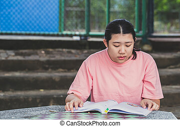 Teen reading book education in the university alone