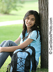 Young teenage girl ready for school. Backpack ready, sitting against tree.