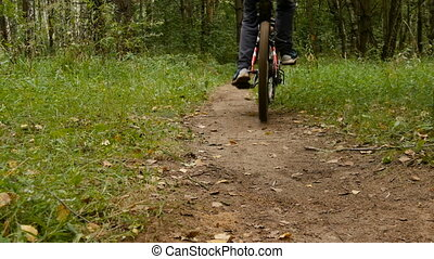 Teen rides a bike through the woods