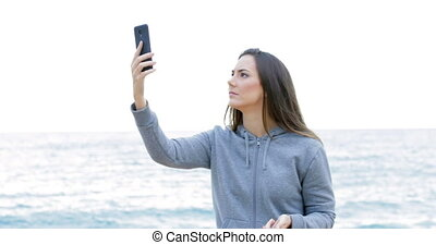Teen searching phone coverage on the beach