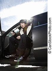 Teen sitting in car.