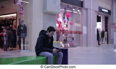 Teen sitting on a bench and playing phone