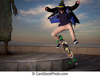 teen skateboarder - young teenager jumping with a longboard