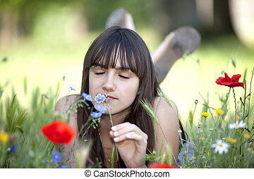teen smelling flower