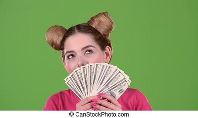 Teen sniffs paper bills and she is delighted. Green screen. Close up. Slow motion