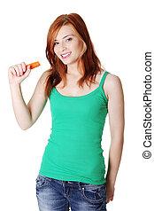 Teen standing girl holding a carrot.