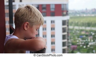 teen stands on the balcony of a tall building and looks down