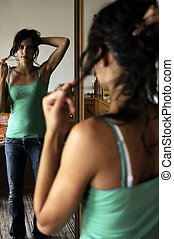 Teen styling - Beautiful teen girl styling her hair in her...