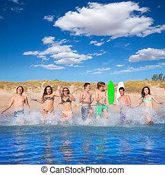 Teen surfers group running beach splashing