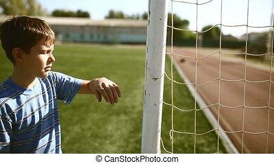 Teen upset defeat boy by knocking goal goal post net stadium...