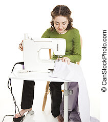 Teen Uses Sewing Machine - Teen girl using a sewing machine...