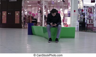 Teen using smartphone on the bench
