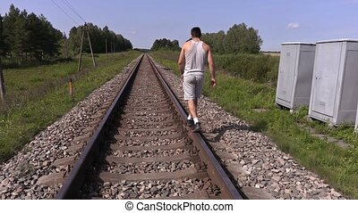 Teen walking away and trying to balance on rails