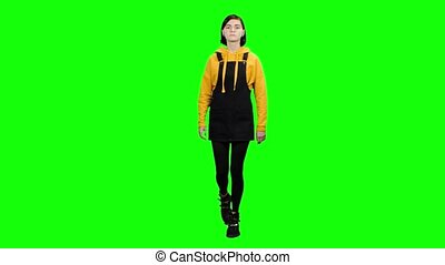 Teen walks and looks at the shop windows. Green screen