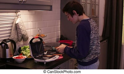 Teen warms up the bread in the toaster