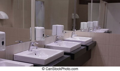 Teen washes his hands with soap in the sink