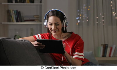 Teen watching and listening media on tablet in the night -...
