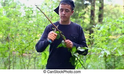 Teen with a knife cuts the branch