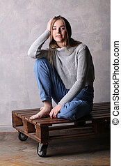 Teen with bended knee sitting on a deck. Gray background