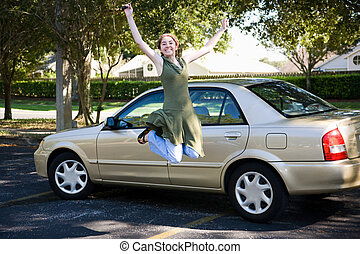 Teen girl with new car jumps for joy.