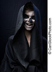 Teen with make-up of skull in black cloak laughs - Teen with...