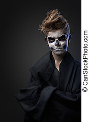 Teen with make-up of the skull in black cape