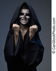 Teen with makeup skull shows fists