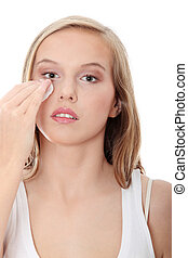Teen woman removing makeup with cleansing pad , isolated on...