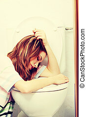 Teen woman vomiting in toilet
