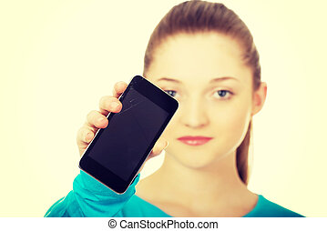 Teen woman with a broken cell phone.