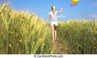 Teen woman with balloons walking in field - Young teen woman...