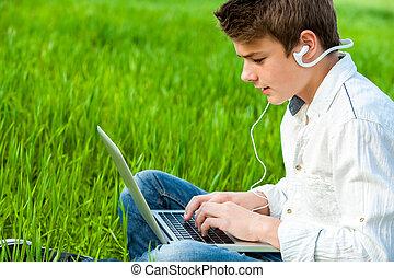 Teen working on laptop in green field.